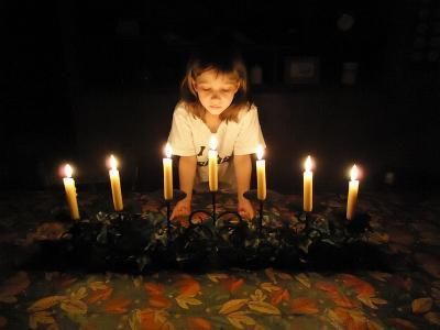 junges Mädchen hinter einem siebenarmigen Leuchter - der jüdischen Menora