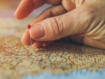 eine Hand steckt eine Stecknadel in eine Landkarte