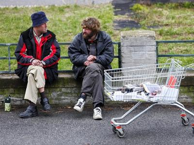 zwei Obdachlose sitzen auf einer Parkbank