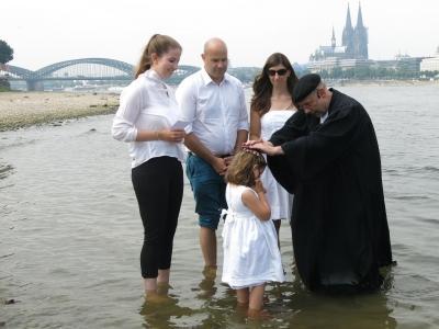 evangelischer Pfarrer tauft Kind im Rhein