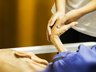 junge Frau hält die Hand eines alten Mannes
