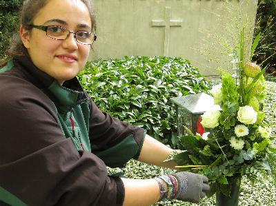 eine Friedhofsgärtnerin bei der Grabpflege