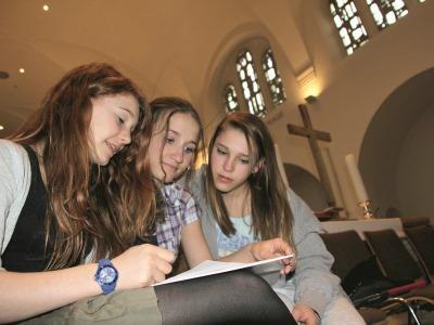 Drei junge Mädchen diskutieren in einer Kirche