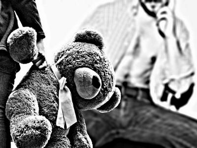 Kind mit Teddy steht vor einem Mann