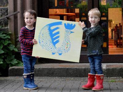 zwei Kinder vor einer Kirchentür halten ein Bild in die Kamera