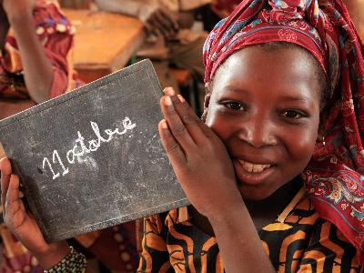 Ein afrikanisches Mädchen hält eine Tafel mit der Aufschrift '11. Oktober'