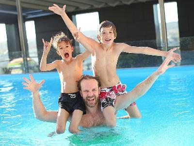 Vater mit zwei Kindern im Schwimmbad