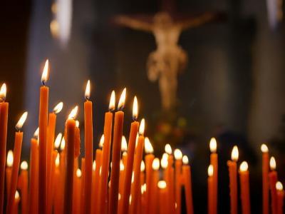 In einer Kirche: brennende Kerzen vor einem Kruzifix