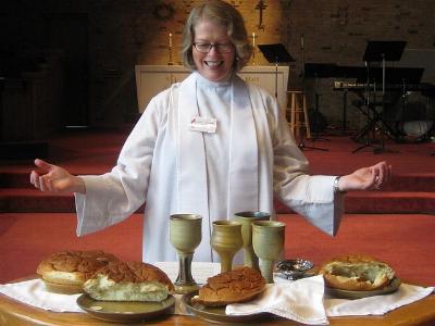 Pfarrerin im weißen Ornat vor einem Altar mit Abendmahl