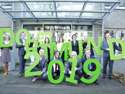 Menschen halten 'Dortmund 2019' in grünen Buchstaben in die Luft