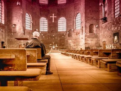 Mann sitzt alleine in einer Kirche