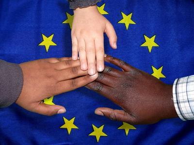 Hände verschiedener Hautfarbe auf EU-Flagge