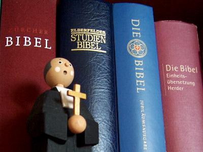 Pfarrer-Püppchen aus Holz vor Büchern