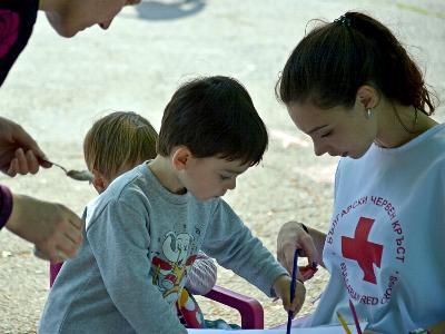 Eine Helferin des Roten Kreuzes spielt mit einem Kind