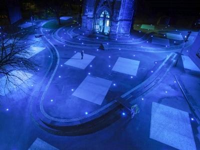 Kirchturm und Vorplatz in blaues Licht getaucht