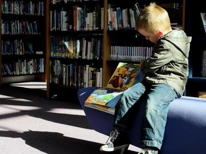 Kind liest in einer Bücherei ein Buch
