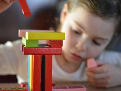 Kind mit wackeligem Turm aus Bauklötzen