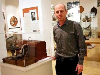 Mann mit alter Nähmaschine in einer Ausstellung
