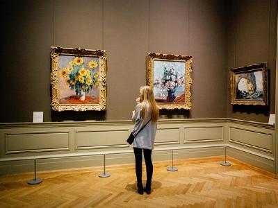 Besucherin vor Bildern in einem Museum