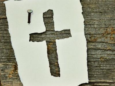 Zettel mit einem Kreuz hängst an einer Kirchentür