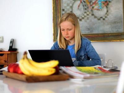 Mädchen mit Laptop macht am Küchentisch Hausaufgaben