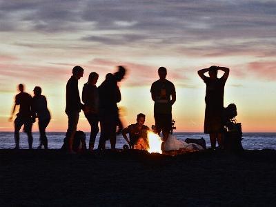 Jugendliche im Abendlicht stehen um ein Lagerfeuer