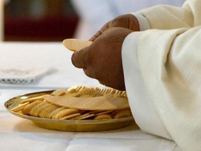 Geistlicher bereitet die Hostien für das Abendmahl