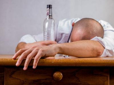 betrunkener Mann mit leerer Schnapsflasche