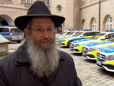jüdischer Rabbiner vor einer Reihe von deutschen Polizeifahrzeugen