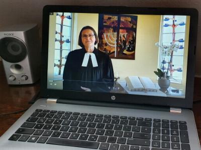 Laptop-Bildschirm zeigt Pfarrerin beim Online-Gottesdienst