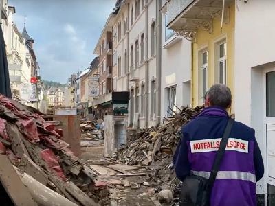 Ein Notfallseelsorger läuft durch eine von den Sturzfluten zerstörte Straße in Bad Neuenahr.