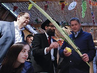 Unter einem mit Stroh gedeckten Dach feiern Juden das Laubhüttenfest
